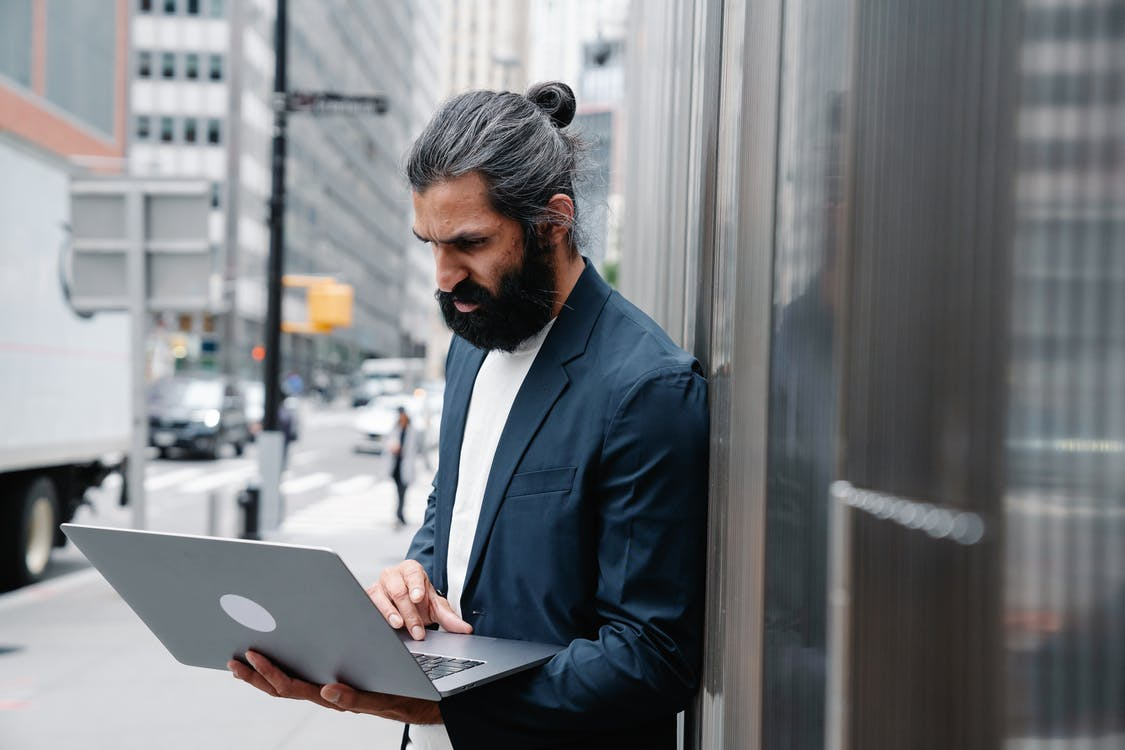Arabic businessman standing on street and using laptop