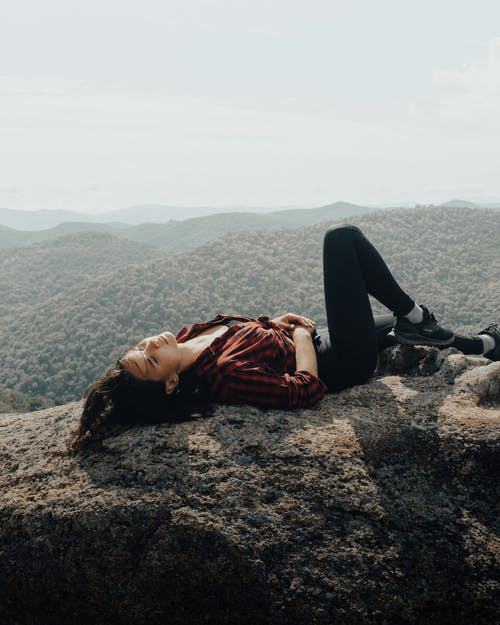 Girl in chequered pattern shirt lying on rock