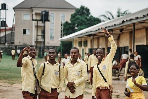 Group of Men in Yellow Uniform Standing on Street