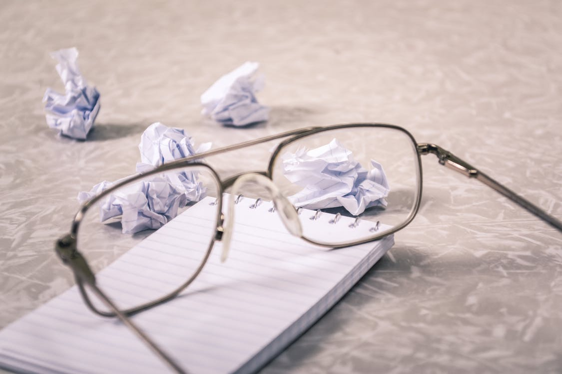 Close-Up Photography of Eyeglasses Near Crumpled Papers