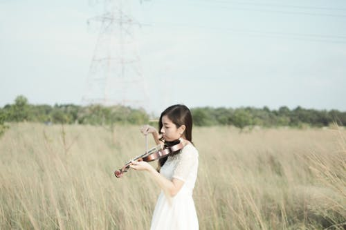 Woman Wearing White Dress Playing Violin