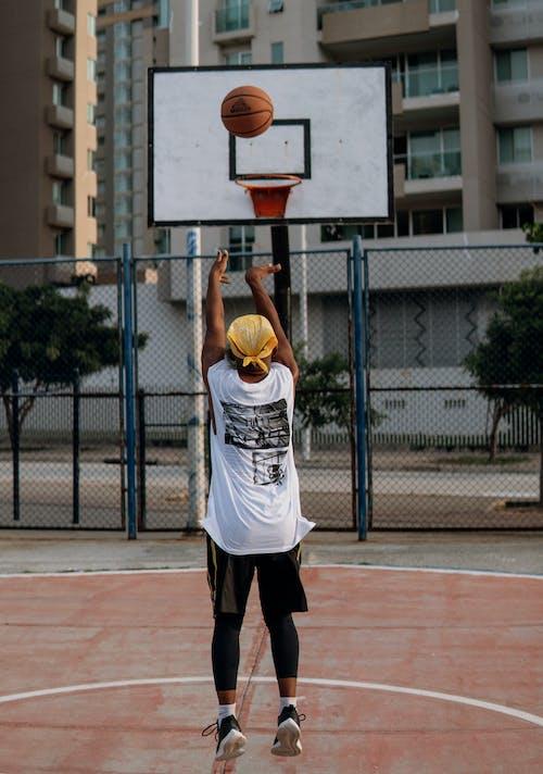 Man throwing ball into basketball ring