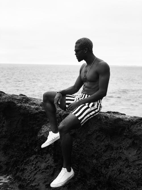 Side view of shirtless man sitting on rock