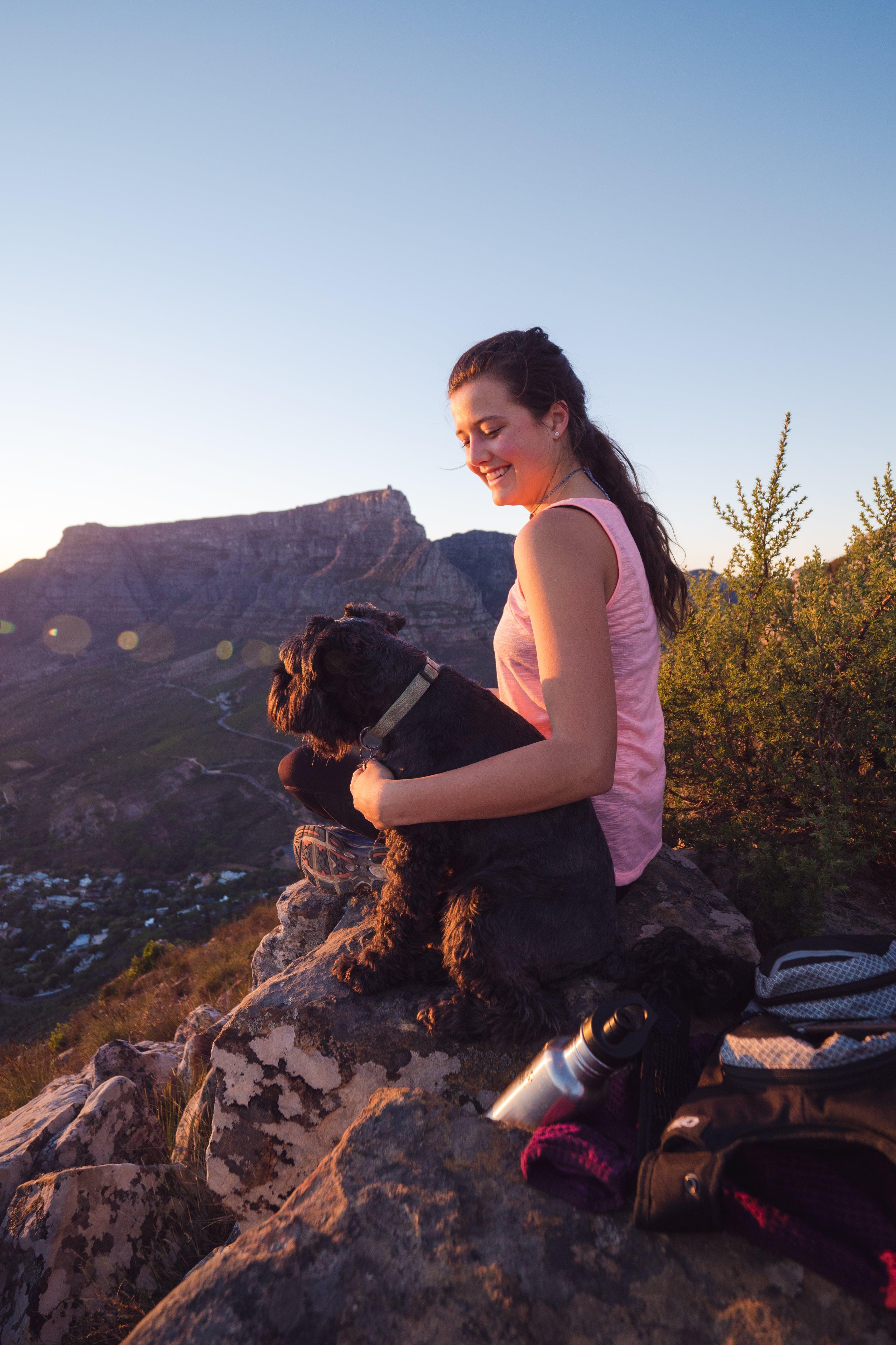 Woman Wearing Pink Tank Top Sitting on Rock Beside Dog