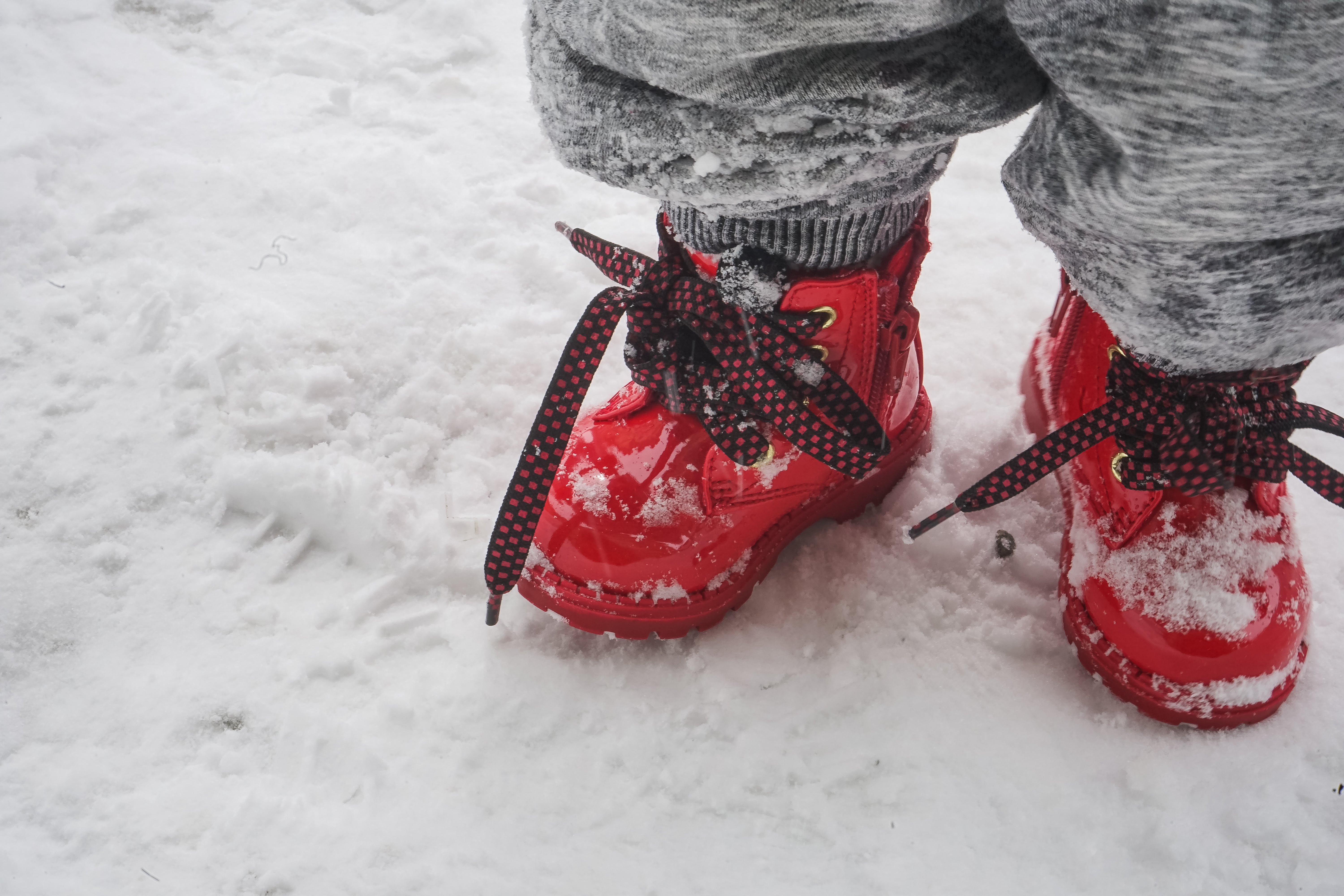 Toddler Wearing Red Shoes Standing On Snow