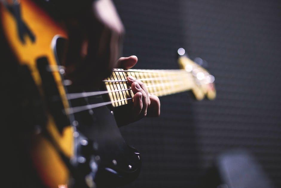 Person playing sun burst electric bass guitar in bokeh photography