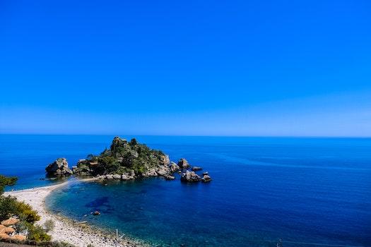White Beach Shoreline Near Gray Rocks Under Blue Sky during Daytime