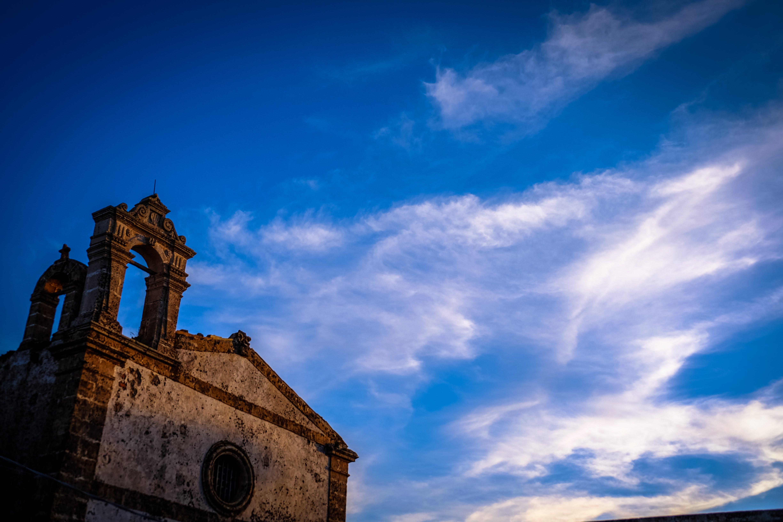 Brown Concrete Chapel Under Cloudy Blue Sky