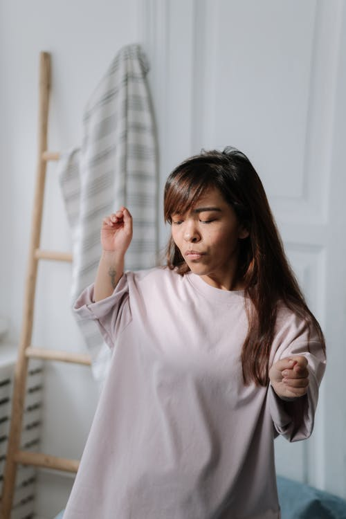 Young dwarf woman listening to music and dancing in her bedroom