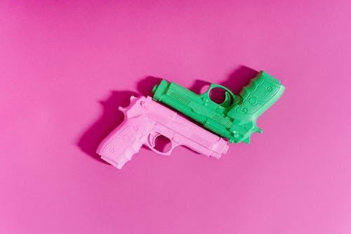 Toy Guns On Pink Surface