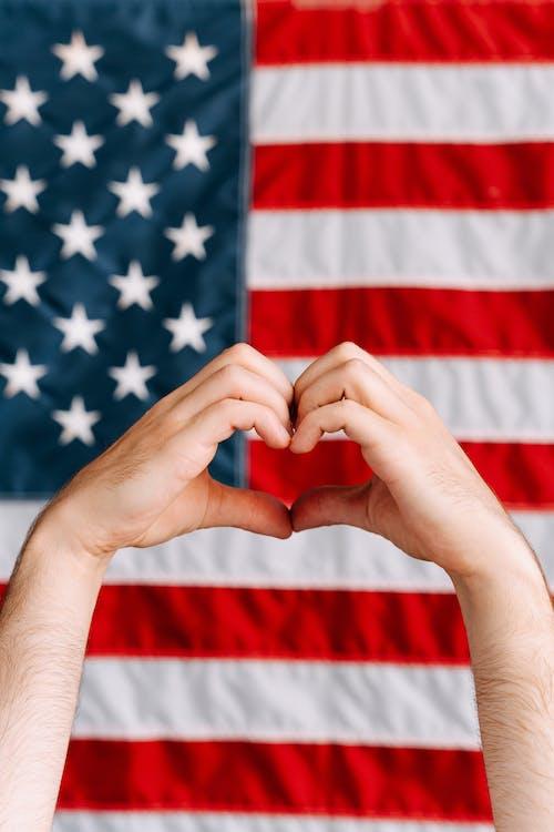 Kostenloses Stock Foto zu amerikanische flagge hintergrund, hände, herz