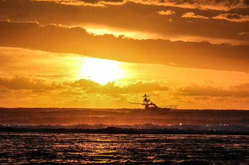 Silhouette Photography of Fishing Boat on Sea during Golden Hour