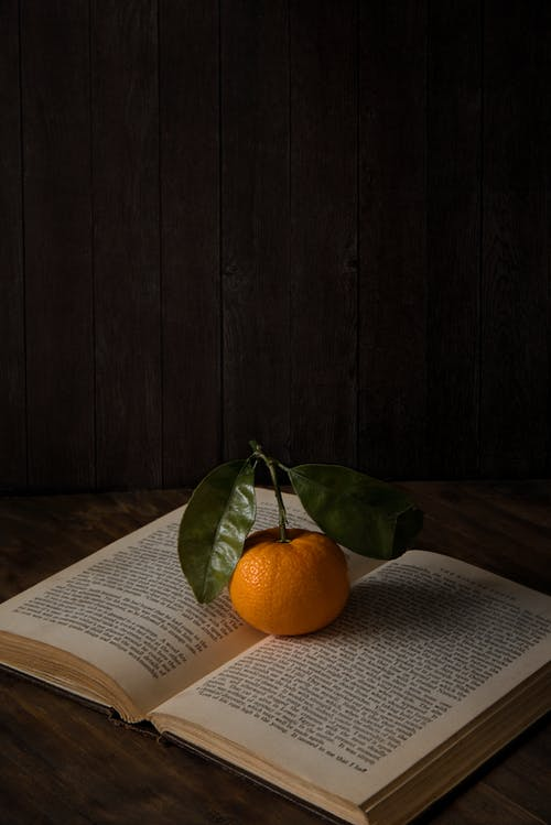 Photo of Orange On Top Of Book