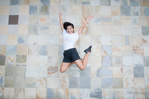 Woman in White Shirt and Black Shorts Taking Jump Shot Near Wall