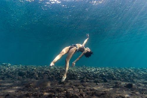 A woman divingunder a water