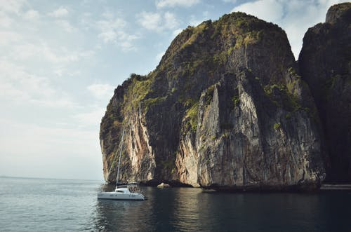 White Sailing Boat Beside Mountain