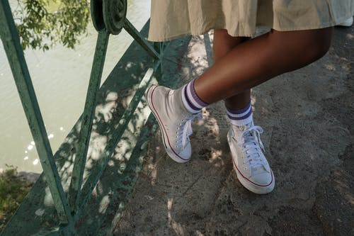 Legs of girl standing on bridge