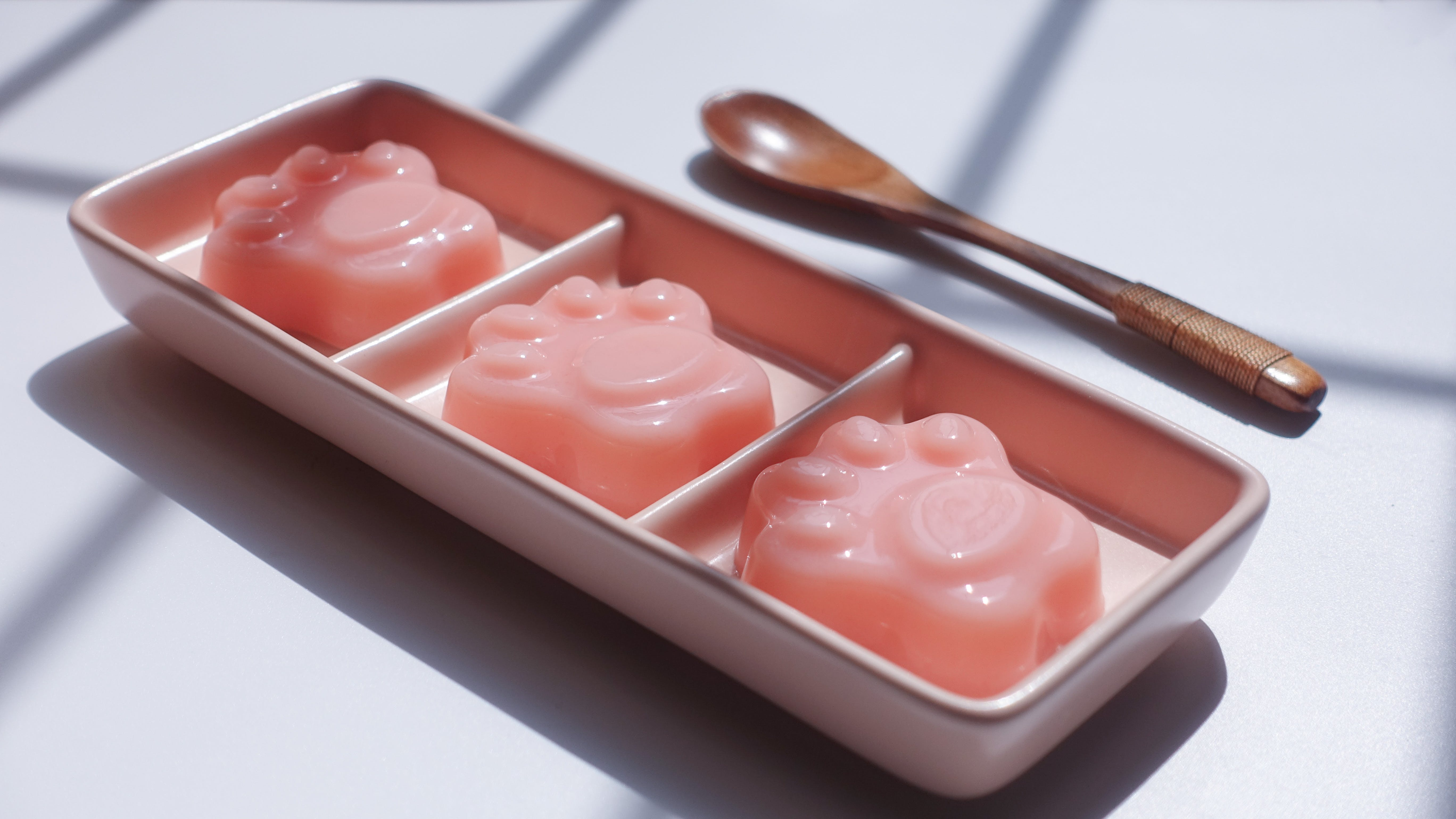 Paw Shape Jell-o on Pink Ceramic Container Near Brown Wooden Tablespoon
