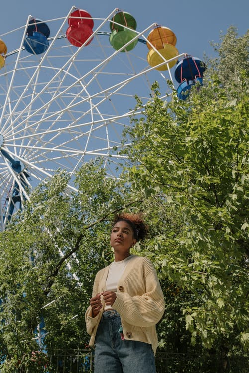 Black girl standing at trees with ferris wheel in background