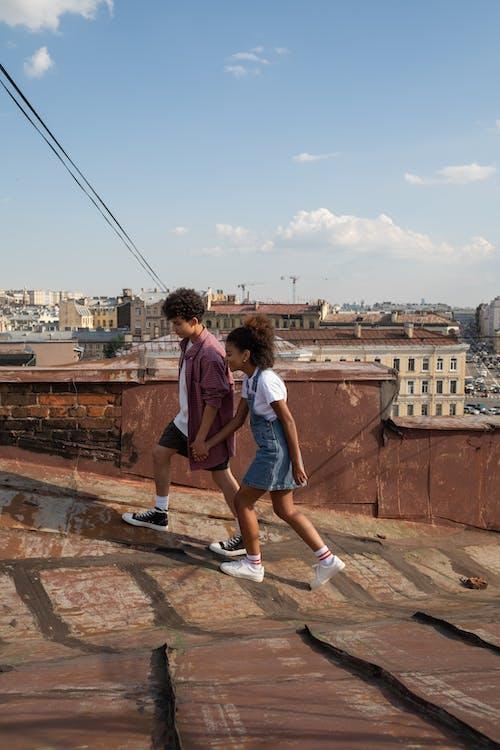 Teenage couple walking holding hands on rooftop
