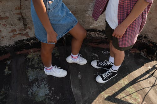Sneakers on legs of teenagers facing each other