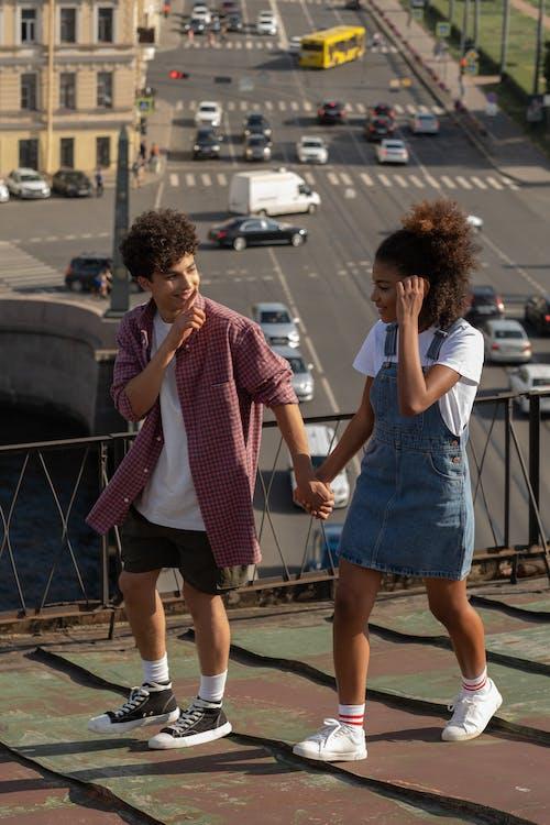Teenage couple walking holding hands on roof
