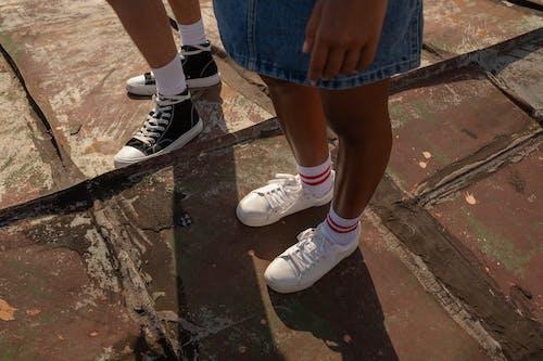 Sneakers on teenagers legs standing on red painted rooftop