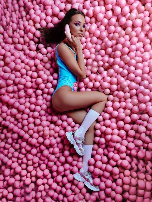 Portrait of woman lying among pink balls