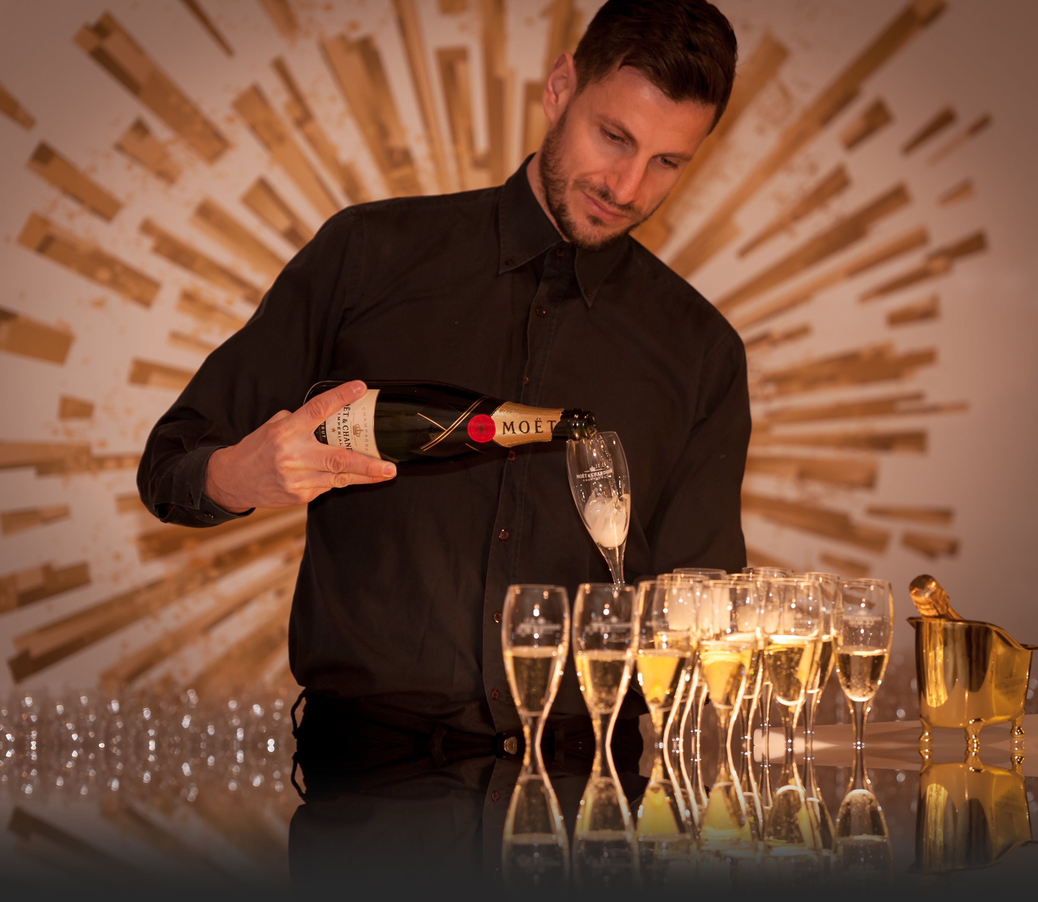 Man Wearing Black Dress Shirt Holding a Flute Glass and Black Wine Bottle
