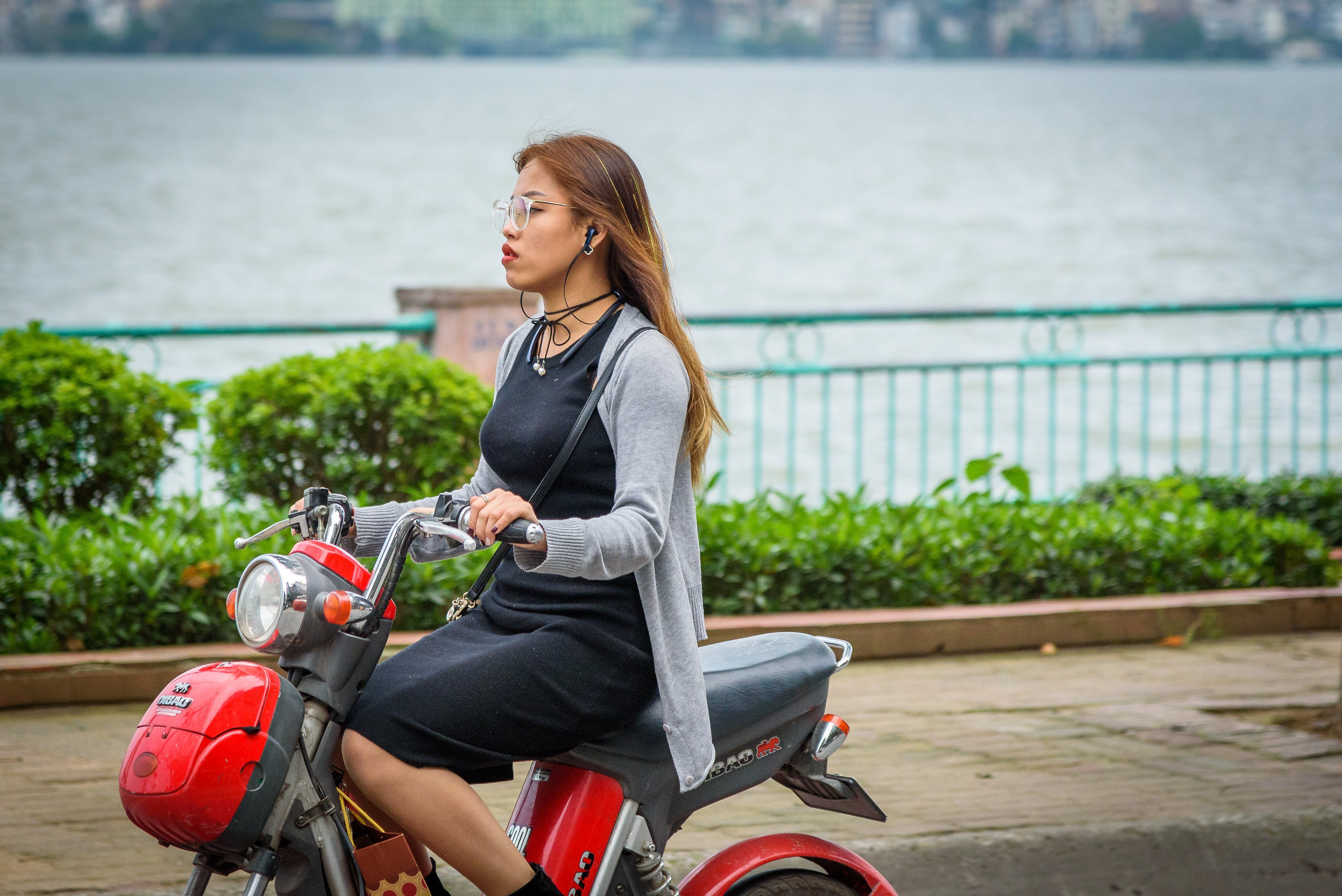 Woman Riding Red Motor Scooter