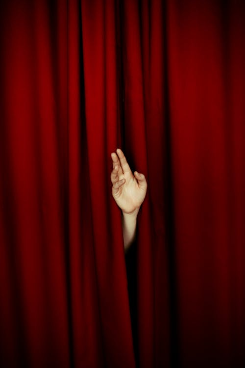Human hand from behind curtain in theatre