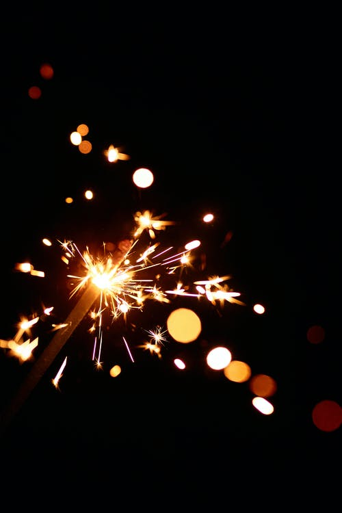 Tip of sparkler shining with dazzling sparks