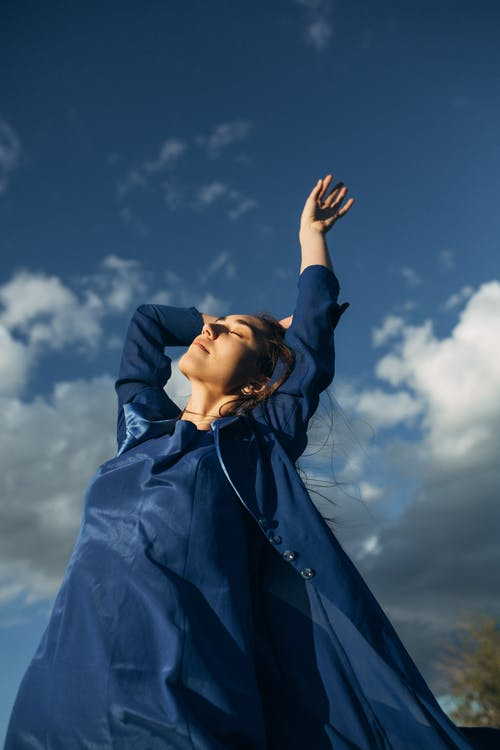Low angle view of woman with hands raised