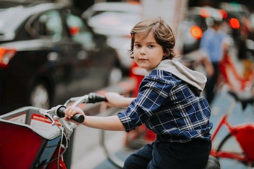 Kid riding on bicycle in big traffic