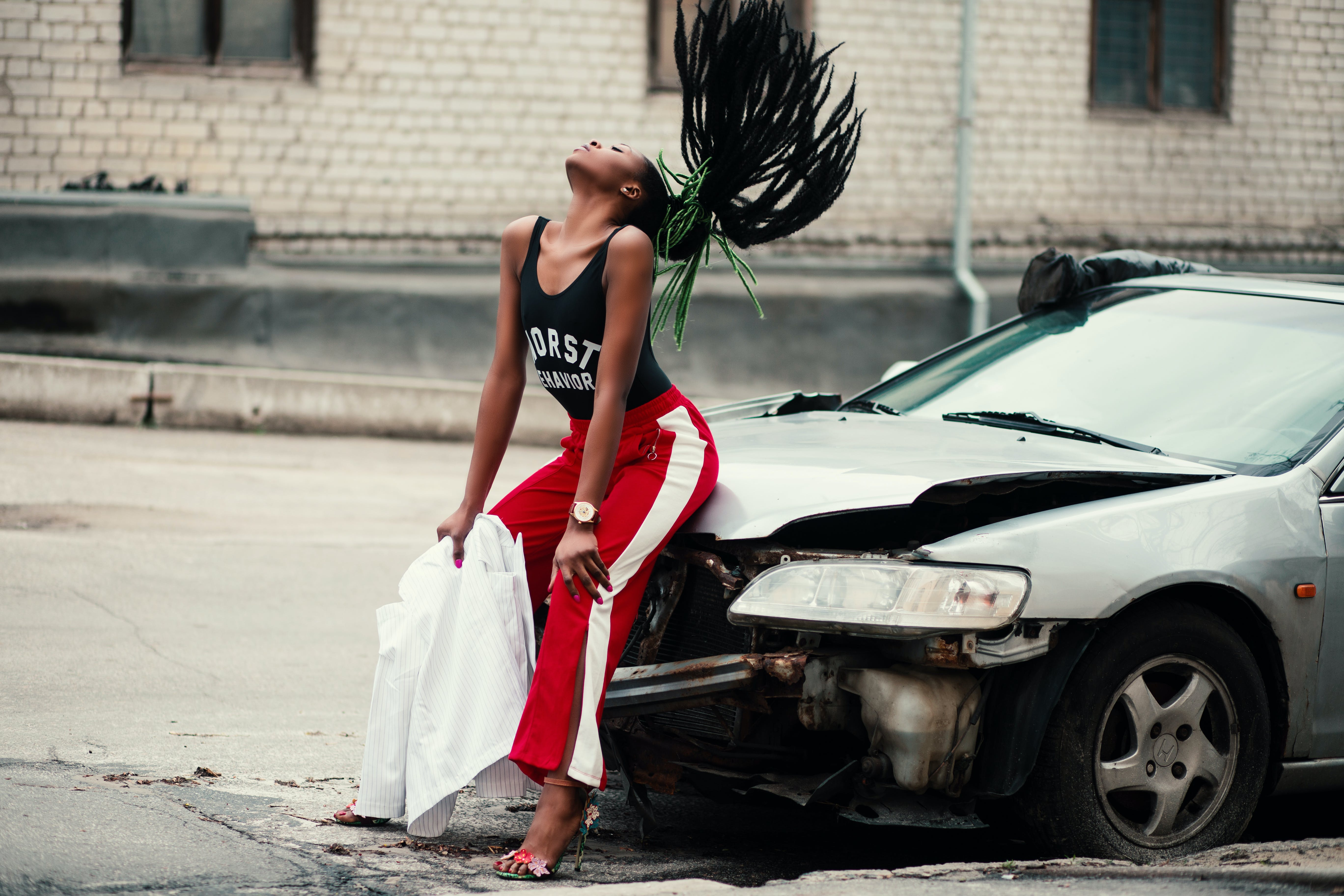Kostnadsfri bild av afrikansk amerikan kvinna, ansiktsuttryck, bil, byxor