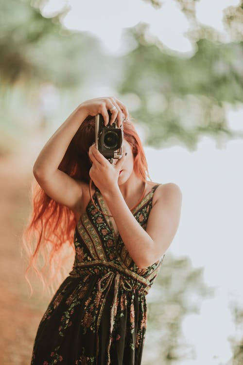 Portrait of redhead woman holding camera in hands
