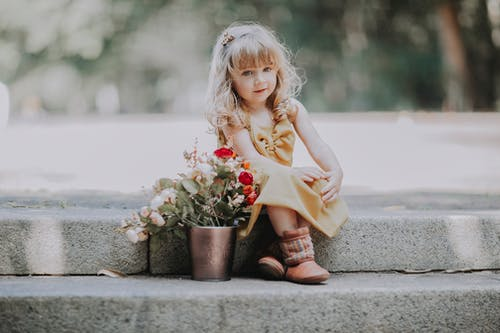 Small girls sitting on stairs with flowers