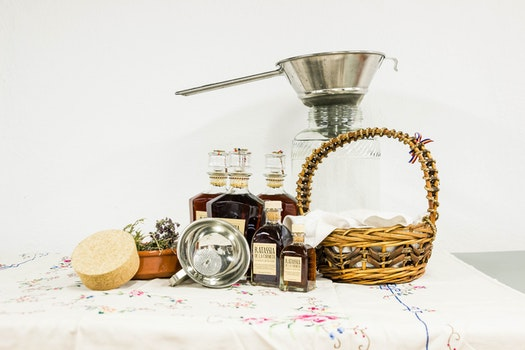 Brown Woven Basket Beside Clear Bottle on White Table Clothe