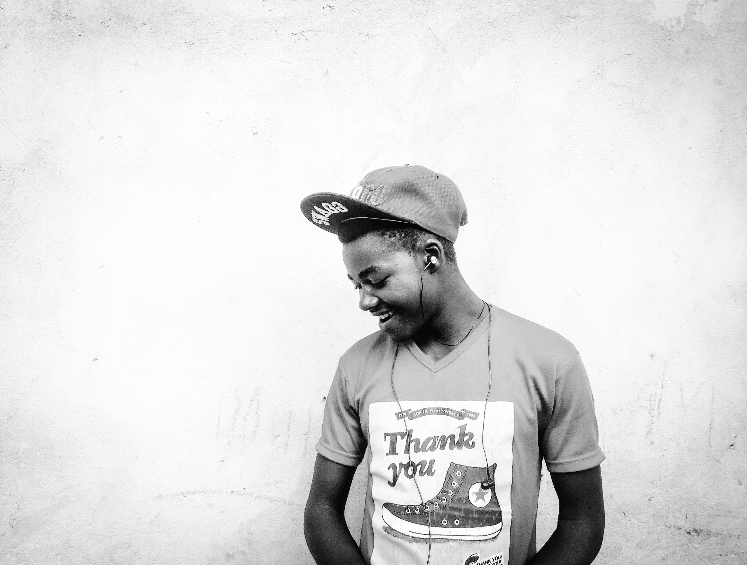 Smiling Man Beside Wall Grayscale Photography