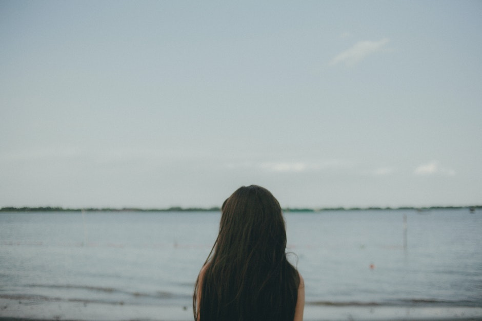 Woman Standing Near Body of Water during Daytime