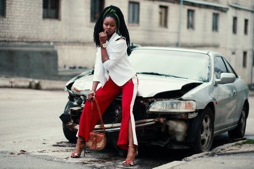 Woman With White Long-sleeved Shirt, Red ,and White Slit Pants and Pair of Black Open-toe D'orsay Heel Sandals Sitting on Wrecked Silver Car