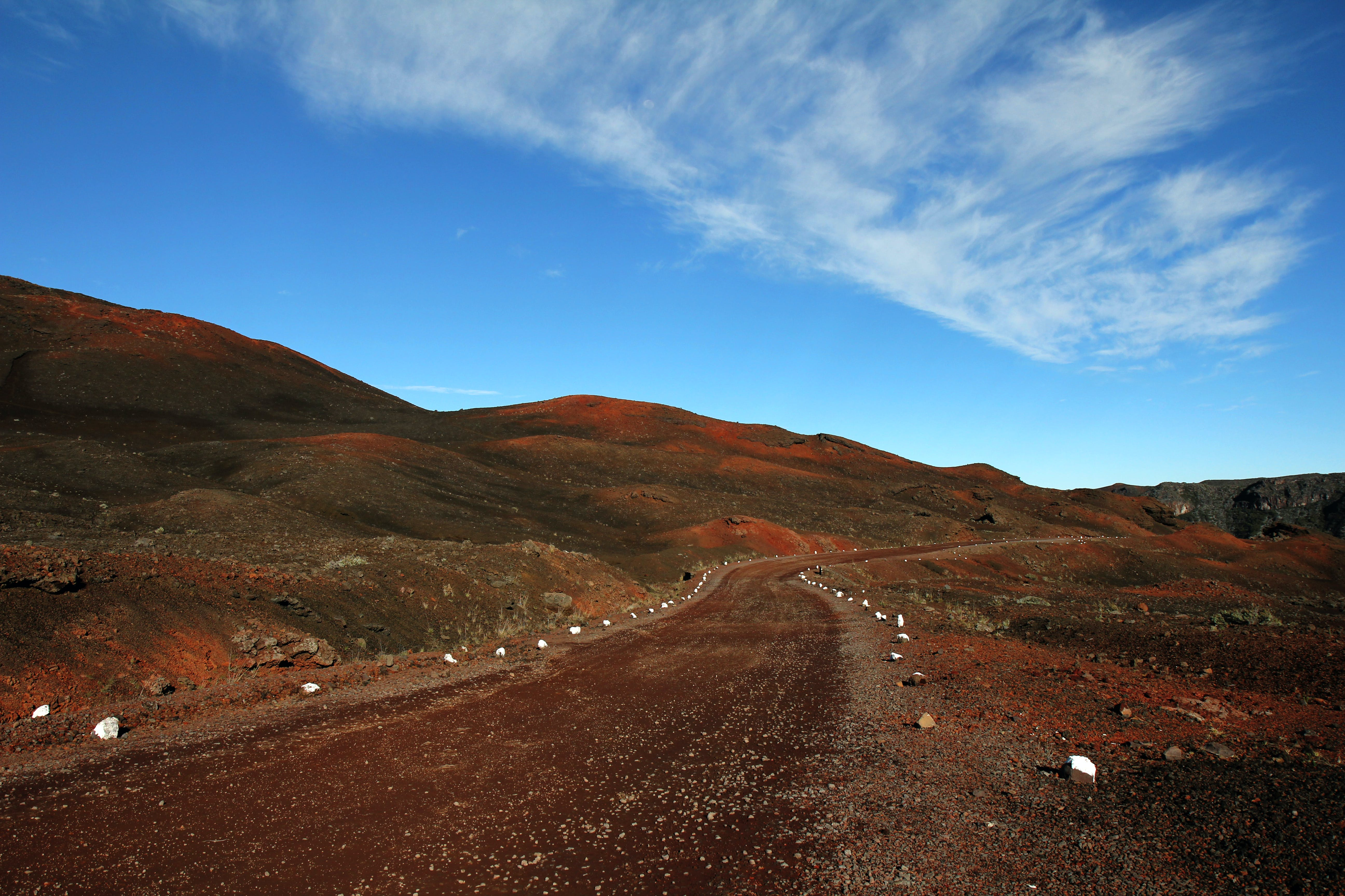 Brown Road Beside Hills over White Clouds and Blue Sky during Daytime