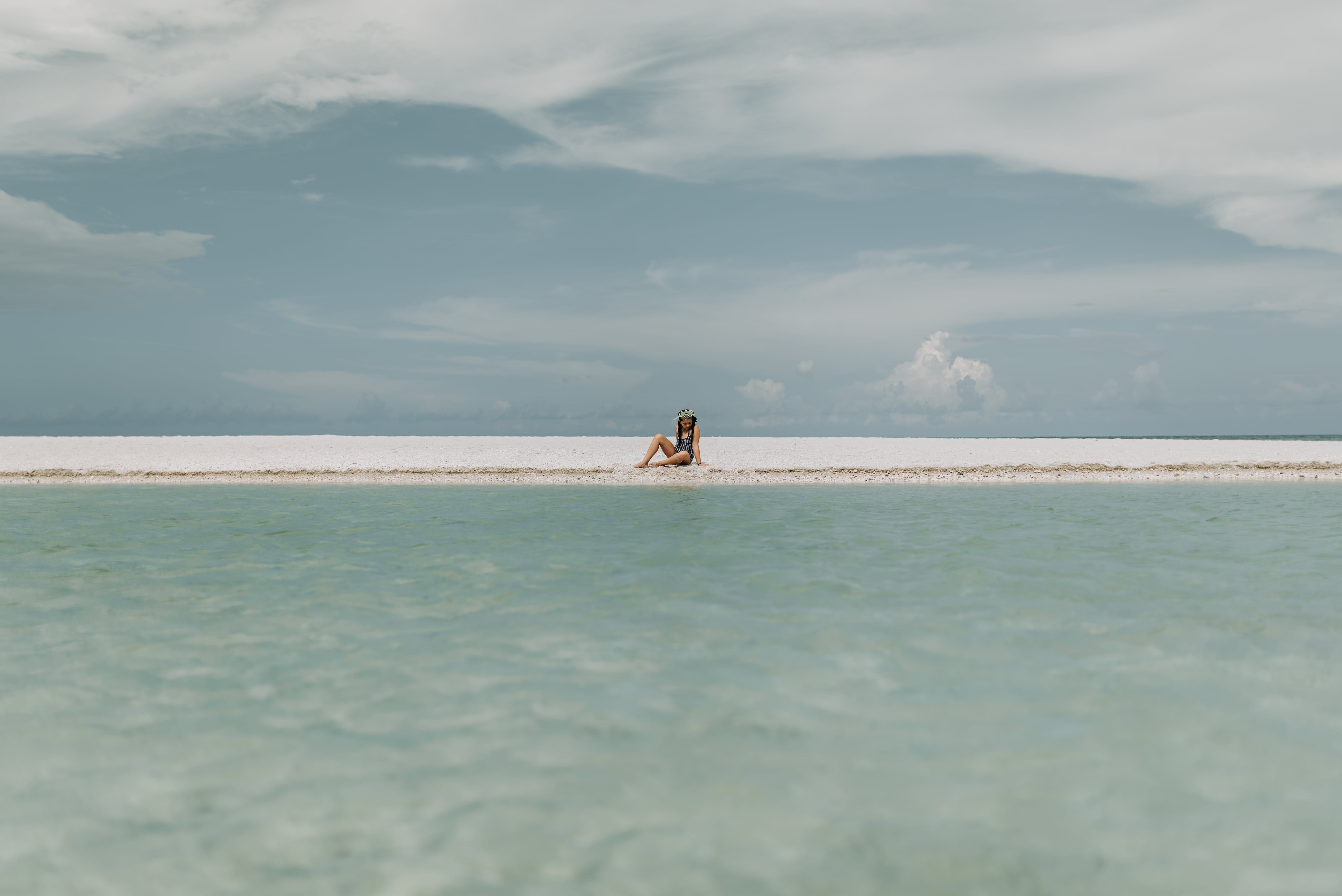 Person Sitting On White Sand