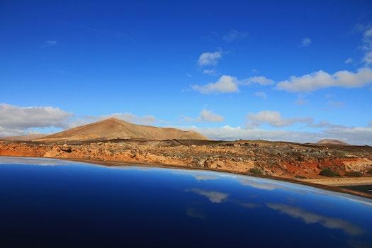 Mountain Beside Body of Water Under Cloudy Sky