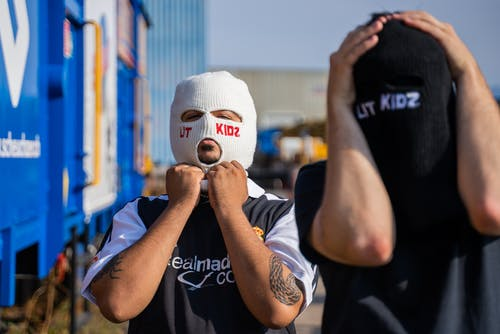 Man in Black T-shirt Covering His Face With White Knit Cap