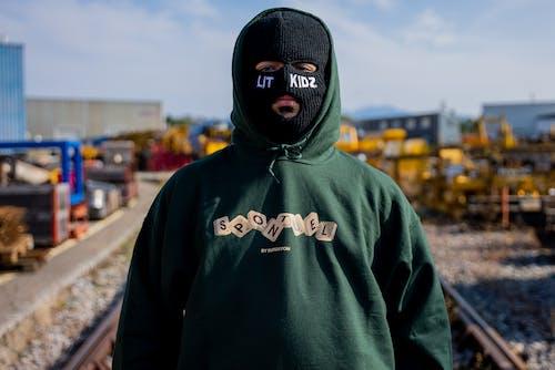 Man in Green Pullover Hoodie Wearing Black Mask