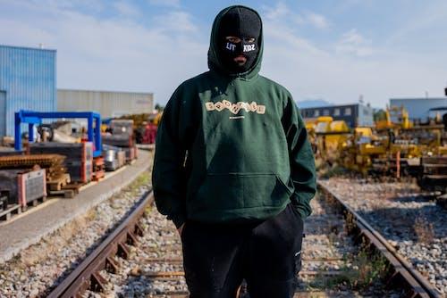 Man in Green Hoodie Standing on Train Rail