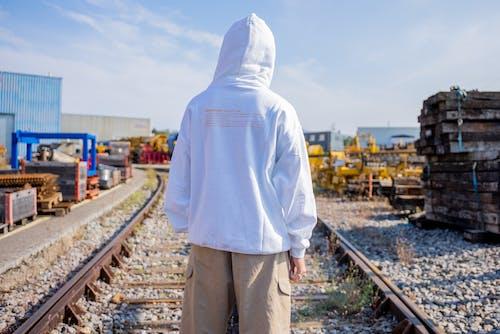 Man in White Hoodie Standing on Train Rail