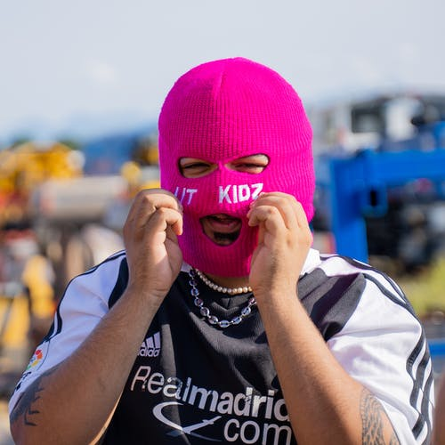 Woman in Pink Knit Cap Covering Her Face With Her Hand