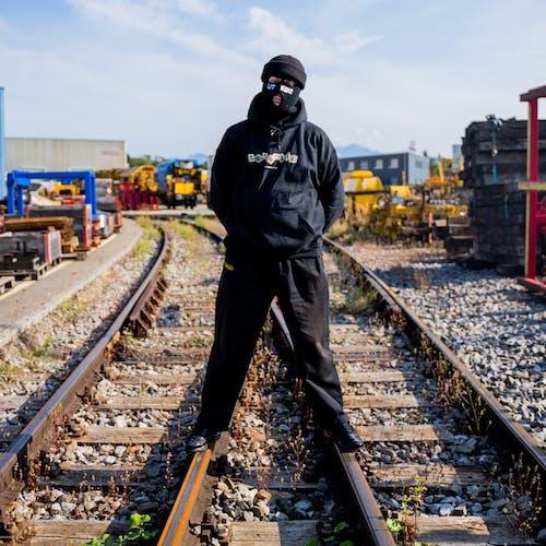 Man in Black Jacket Standing on Train Rail